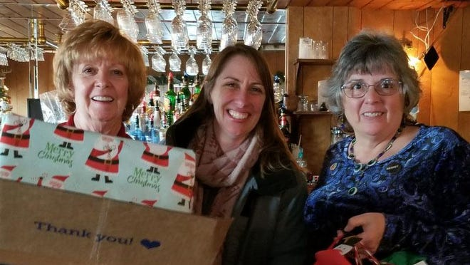 Suzy McCormack, center, from Cornell Cooperative's Relatives As Parents Program accepts gifts of children's clothing from MARTA members,Gail Cocks and Mary Lou Deitrich.