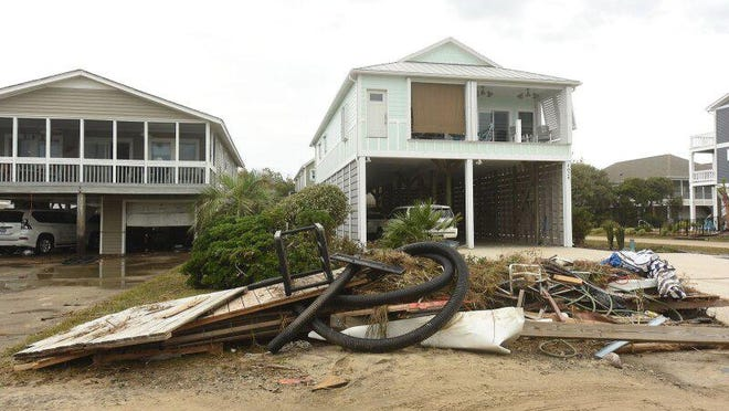 Crews and residents continue to clean up Wednesday along Oak Island after Hurricane Isaias.
