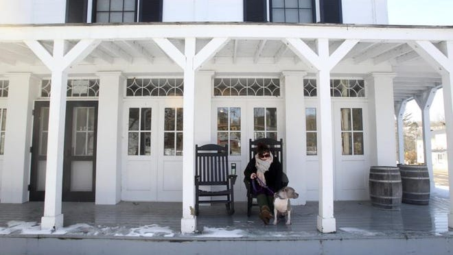 A woman and her dog sit on the porch of the Boston Store Visitor Center in this file photo. The store at 1550 Boston Mills Road in Peninsula is the meeting place at 9:30 a.m. Saturday for an Akron Metro Parks Hiking Club 7-mile hike. More information at