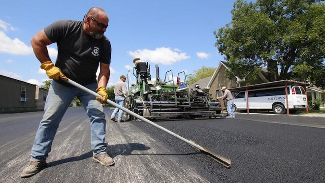 Dewey Grider, who owns Grider Paving -- formerly the Prater company -- works with his crew in the parking lot at Midtown Church, where the company paved the church's parking lot.