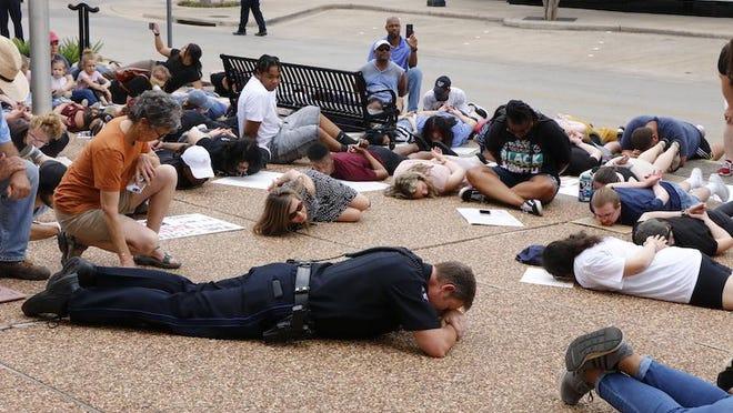 Brownwood police Lt. James Kidd lies with protestors outside City Hall Monday.