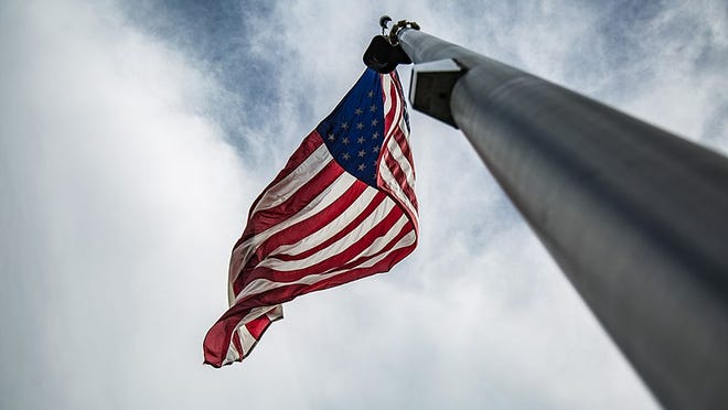 The American flag hanging on a flag pole blowing in the wind in Washington.