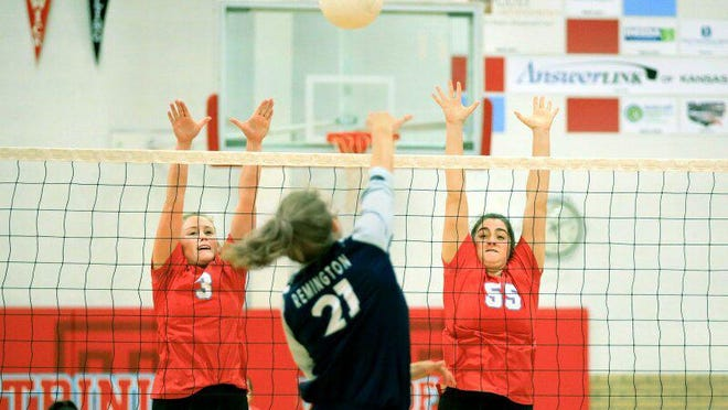 Trinity's Emily Dilbeck (3) and Karolyn McConnaughy (55) blocks the spike of Remington's Desiree Ingalsbe (21) Tuesday evening. Remington defeated Trinity in the first match 25-23, 27-25.