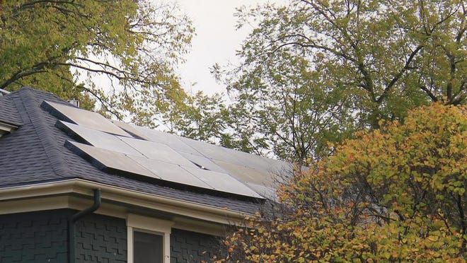 Solar panels line the roof of a home in Lawrence.