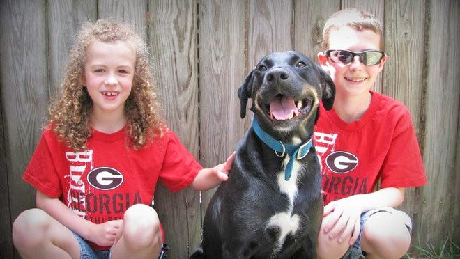 Aubrey and Emory DeLoach are pictured with their dog Leia seven years ago, shortly after bringing her home.
