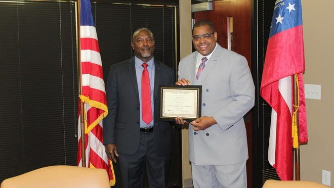 Richmond County Sheriff's Investigator Cecil Ridley (left) receives an award for five years of distinguished service from Sheriff Richard Roundtree