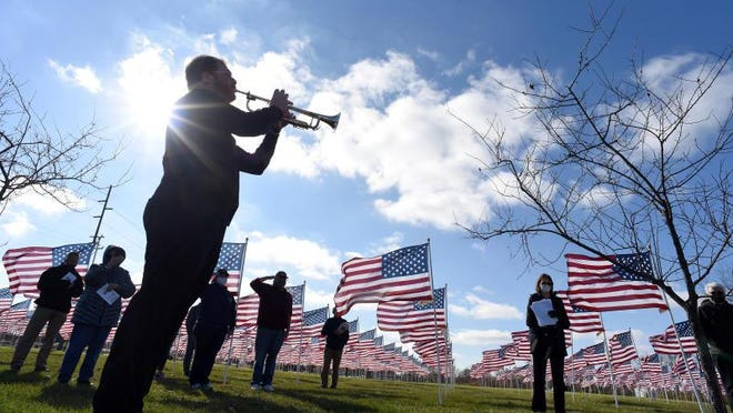 "Ryan Jewell plays Taps to close the Veteran Day Ceremony and Recognition of the Fallen at the ""Flags of Honor"" display. Featuring 500 American flags, the display is presented by the Monroe Exchange Club in partnership with the River Raisin National Battlefield Park."