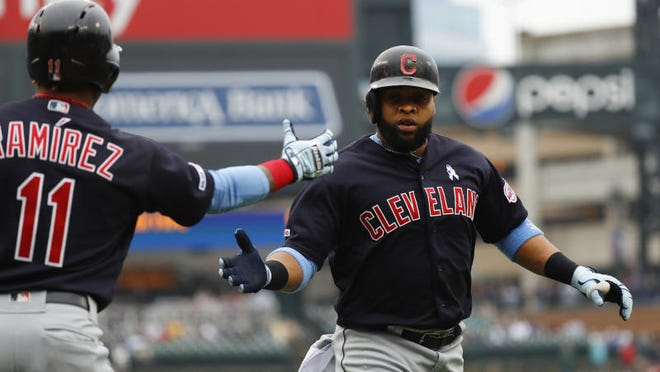 Cleveland Indians' Carlos Santana celebrates scoring with Jose Ramirez (11) against the Detroit Tigers in the first inning of a baseball game in Detroit, Sunday, June 16, 2019.