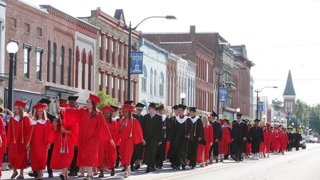Marshall High School seniors parade through downtown Marshall before their graduation ceremony Saturday evening.