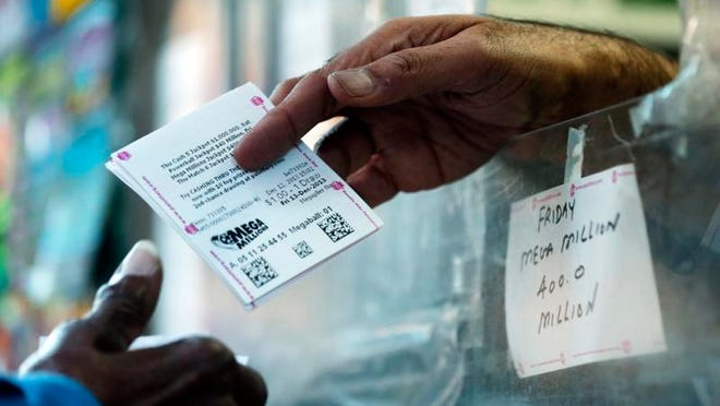 A woman buys Mega Millions lottery tickets at a newsstand in Philadelphia in this Feb. 19, 2014, file photo.