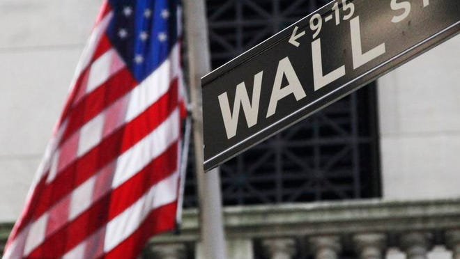 This Monday, July 15, 2013 file photo shows the American flag and Wall St. street sign outside the New York Stock Exchange, in New York. A listless day of trading left the stock market with a tiny loss for the week, its second this month.