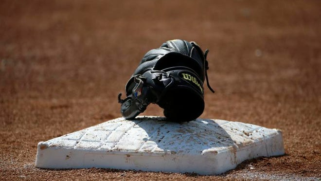 A Wilson baseball glove sits on third base during Baltimore Orioles batting practice before an exhibition spring training baseball game against the Philadelphia Phillies in Sarasota, Fla., Friday, March 7, 2014. (AP Photo/Gene J. Puskar)