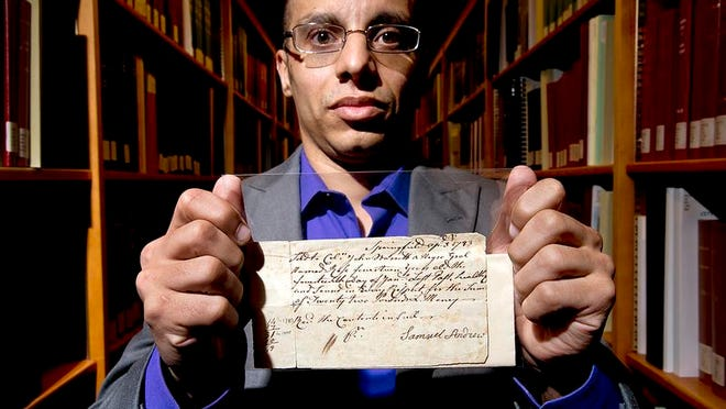 Harvey Amani Whitfield, associate professor of history at the University of Vermont, has written a book on slavery in Vermont.  He holds a 1783 bill of sale for a slave named Rose at UVM's Special Collections in Burlington on Monday, March 24, 2014.