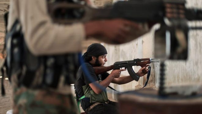 Rebel fighters from the Islamic Front, Syria's largest rebel coalition, hold a position Sunday during clashes with militants of the Islamic State for the control of a village on the outskirts of Aleppo.