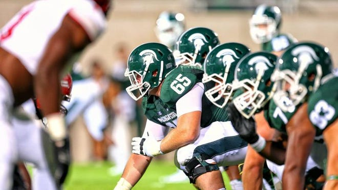 Michigan State center Brian Allen (65) prepares to snap the ball against Jacksonville State on Aug. 29, 2014.