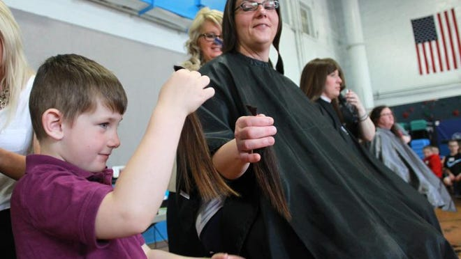Above: Blayke Aldert checks out his mom's donated hair as she gets a cut Wednesday during a Locks of Love event at Clear Creek Elementary in Oxford.