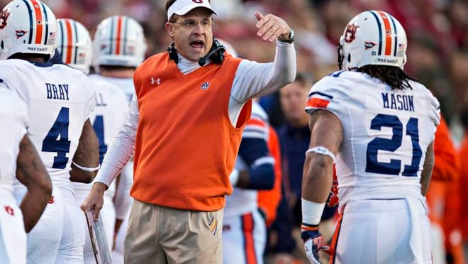 Auburn coach Gus Malzahn congratulates Tre Mason after a touchdown against Arkansas in early November. The Tigers will find out how well they stack up against unbeaten Alabama this week.