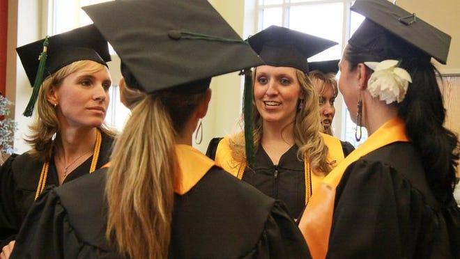 Facing camera left to right, Debra Baker and Amy Bell speaking to, facing away from camera left to right, Shannon Bane-Prasil and Laurie Bishop during the Ivy Tech graduation at Northside Christian Church in New Albany, IN. (By Frankie Steele, Special to The Courier-journal) May 13, 2011