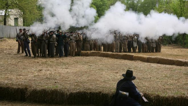 Civil War re-enactors take part in a firing demonstration on the reclaimed land that was formerly the garden at the Carter House in Franklin in 2010.