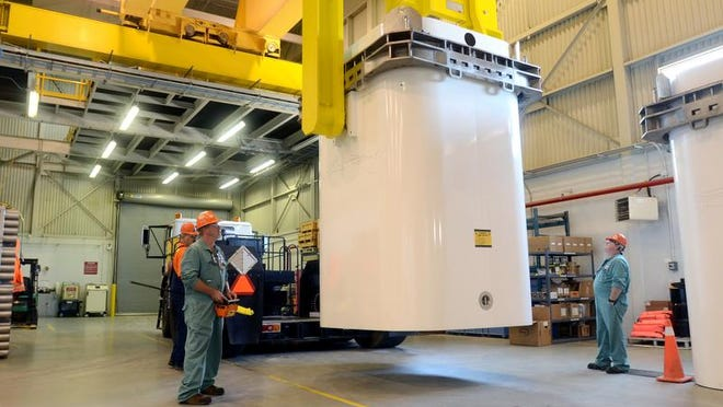 Workers unload a fuel cell container inside the used fuel dry storage facility at the Ontario Power Generation's Bruce Power Site in Kincardine, Ontario.