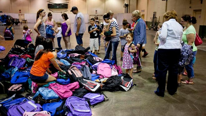 Kids and parents look over a pile of backpacks during the Community Foundation of St. Clair County backpack and school supply giveaway Wednesday at McMorran Place in downtown Port Huron.