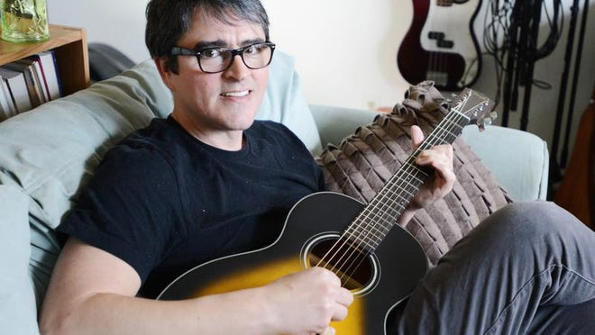 Noah Hall, a local musician, singer/songwriter, plays the guitar at his South Salem home on Wednesday. Hall has a new album being released at the beginning of May. He has three kids, and is a stay-at-home dad with his youngest.