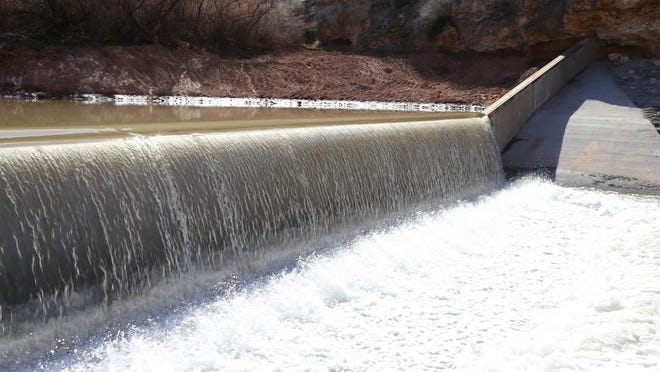 The waters of the Virgin River spill over a concrete fish barrier  near the Utah-Arizona border south of St. George.