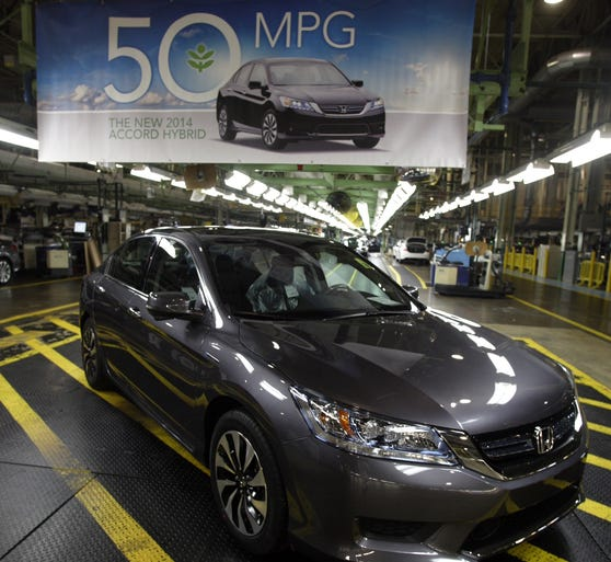 The 2014 Honda Accord hybrid at the Marysville, Ohio, with a banner boasting of its 50 mpg EPA rating for city driving.
