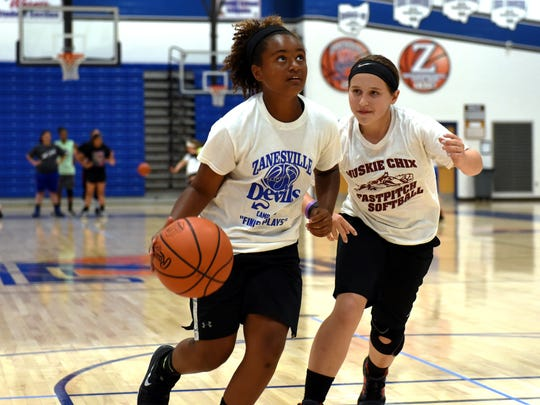 Jersey Draughn drives to the basket while classmate Kamrie Simon guards her during a 1-on-1 drill on Tuesday during Zanesville Lady Devils Basketball Camp. Both girls are sixth graders at John McIntire Elementary.