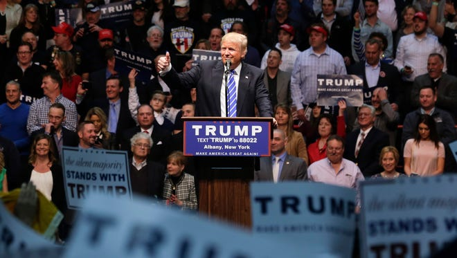 Republican presidential candidate Donald Trump speaks during a rally at the Times Union Center on Monday, April 11, 2016, in Albany, N.Y. State Sen. Fred Akshar, in a grey suit jacket and blue shirt, can be seen to the right of the podium. (AP Photo/Mike Groll)