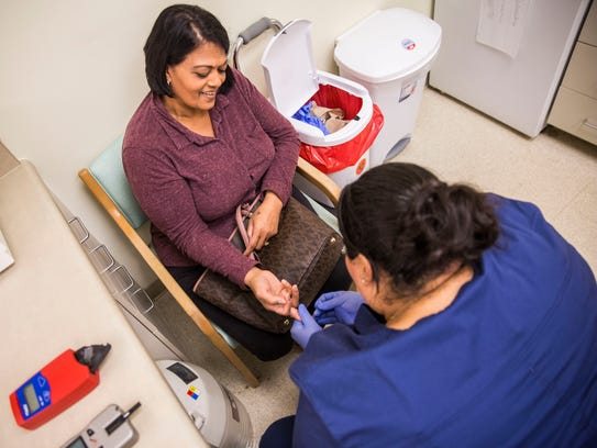 Sharlene Ali, left, gets blood work done by lab assistant