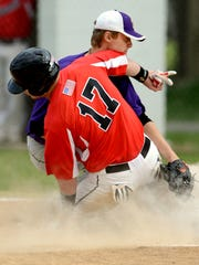 Bennett's Josh Wyatt safely slides under the tag of Crisfield pitcher Caleb Evans to score as he covers the plate on a passed ball.