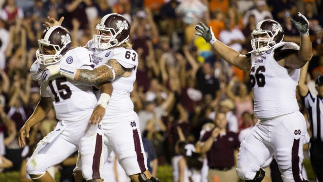 Mississippi State offensive lineman Dillson Day (63) and Ben Beckwith (66) celebrate with quarterback Dak Prescott.