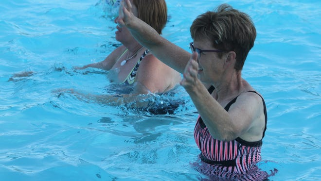 Denise Heitman (left) and Teri Daines move their arms and legs during the water aerobics class Monday, July 2, at Marengo Municipal Swimming Pool.