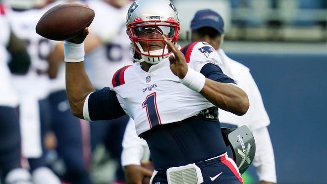 New England Patriots quarterback Cam Newton passes during warmups before an NFL football game against the Seattle Seahawks, Sunday, Sept. 20, 2020, in Seattle.