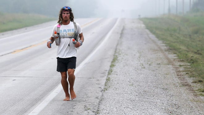 Jake Brown runs toward Avilla on Historic Rt. 66 on Tuesday, July 7, 2015. Brown is running barefoot across the country.