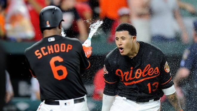 The Orioles' Manny Machado celebrates with teammates after hitting the game-winning grand slam in the ninth inning against the Los Angeles Angels on Friday night.