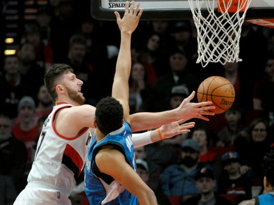 FILE - In this March 25, 2017, file photo, Portland Trail Blazers center Jusuf Nurkic drives to the basket on Minnesota Timberwolves center Karl-Anthony Towns during an NBA basketball game in Portland, Ore. The Blazers upgraded Nurkic to doubtful for Game 3 of their playoff series against the Golden State Warriors. The Warriors have a 2-0 lead in the series, which shifts to Portland on Saturday night, April 22. Nurkic missed the final seven games of the regular season and the first two playoff games at Golden State because of a nondisplaced fracture in his right leg. (AP Photo/Steve Dykes, File)