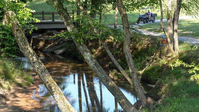 Gilder Creek runs under State Highway 14 in Simpsonville, near a man riding in a golf cart at Holly Tree Golf Club.
