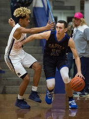 Castle's Alex Hemenway (12) dribbles past Reitz's Kristian Lander (4) as the Reitz Panthers take on the Castle Knights at Reitz High School in Evansville, Ind., on Friday, Dec. 15, 2017. Castle won 71-53.