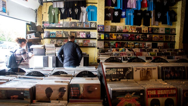 Patrons browse and purchase vinyl records Wednesday April 13, 2016 inside local record store Static Age, located on North Lexington Avenue.