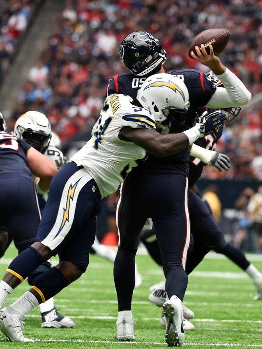 Houston Texans quarterback Brock Osweiler is hit by San Diego Chargers' Melvin Ingram as he throws during the first half of an NFL football game Sunday, Nov. 27, 2016, in Houston. (AP Photo/Eric Christian Smith)