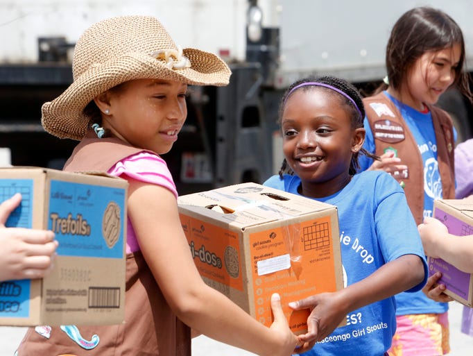 Celina St. Vil, 9, of Ossining, left, with Brownie Troop #1606 passes a box to Ava Barnaby, 8, of Stony Point with Brownies Troop #40465 as Girl Scouts load up a van as part of Girl Scouts Heart of the Hudson's Operation Cookie Drop, June 14, 2014 at the Westchester Police Academy in Valhalla. Girl Scouts, adult volunteers, ROTC, local servicemen and service women loaded up vans of donated cookies to be delivered to troops overseas, in hospitals and in veteran's homes.