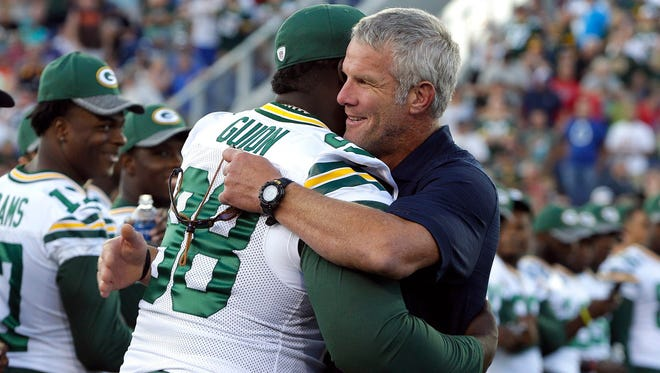 Former Packers quarterback Brett Favre gets a hug from Packers defensive lineman Letroy Guion on Sunday in Canton, Ohio.