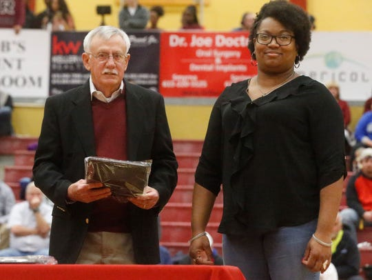 Former Riverdale head girls basketball coach Keith Short presents former player Angela Garrett with a plaque commemorating Garrett being inducted into the Lady Warrior Hall of Fame Tuesday.