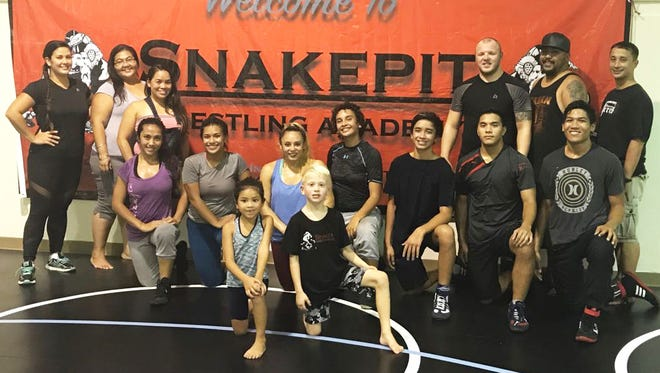 Former Olympians Maria Dunn, far left, and Nathan Tully, third from right, will accompany a team of nine wrestlers on a two-week wrestling tour that takes them to the origins of their team name in England. They are shown at the Snakepit Wrestling Academy in Tiyan on July 4. Pictured back row, left to right, Dunn, Geralyn Stanley, Therese Diaz, Tully, Peter Gutierrez, George Diaz. Middle, left to right, Tammy Torres, Stacy Falagoy, Amanda Aguero, Bobbie Larrison, Jonah Diaz, Liam Hocog, Terrence Harris. Front row, left to right, Taome Gutierrez and Jackson Nuner.