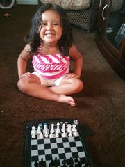 Ronald Olverson Jr. is teaching his granddaughter, Amaiya Villada, 3, how to play chess as part of his efforts to prepare her for college.