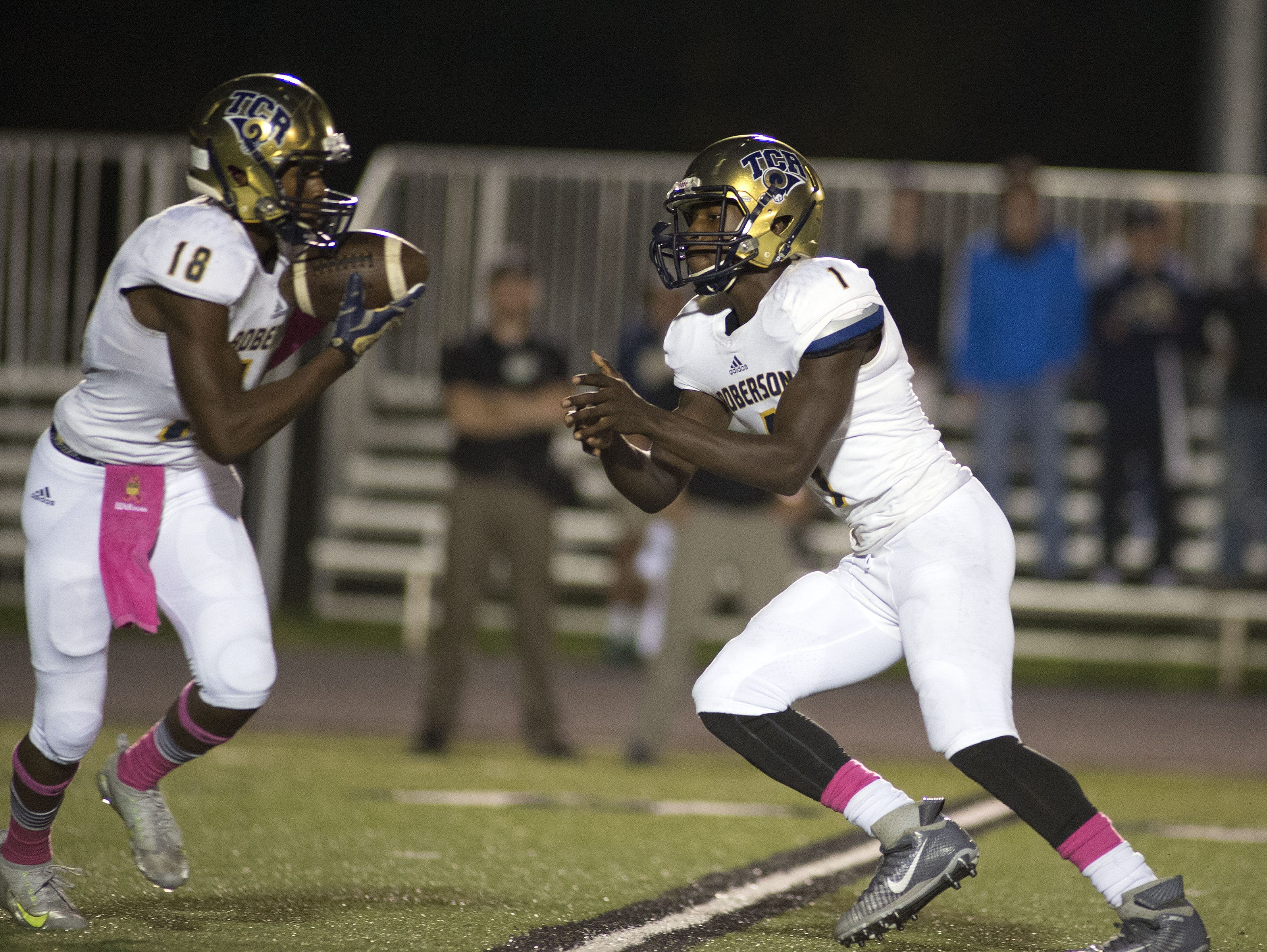 Roberson quarterback Eric Robinson (1) pitches the ball to Dezmond Moorman during Friday's 27-24 loss at North Buncombe.