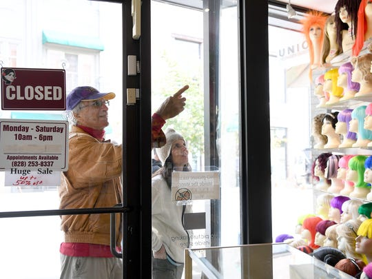 Ed Weintraub, of Chapel Hill, and Cathy Casella, of Cary, window shop outside of Kim's Wig Center on Monday, Oct. 16, 2017. The iconic store will be closing in December.