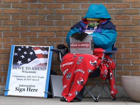 A Wisconsin volunteer tries to stay warm as she collects signatures for the Move To Amend campaign on April 1 in Appleton.